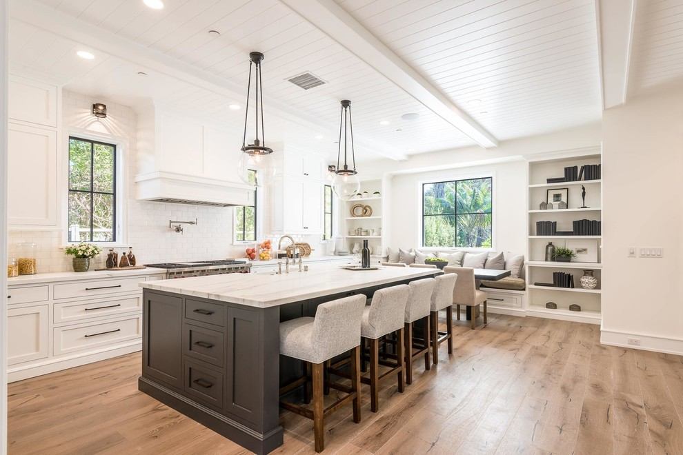 Example of a transitional l-shaped medium tone wood floor and brown floor eat-in kitchen design in Los Angeles with shaker cabinets, white cabinets, white backsplash, subway tile backsplash, stainless steel appliances, an island and white countertops