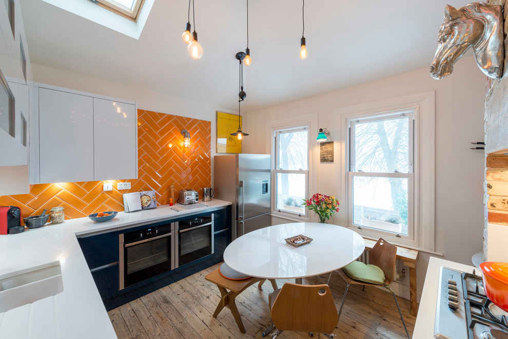 Inspiration for a mid-sized eclectic u-shaped medium tone wood floor and brown floor eat-in kitchen remodel in London with an undermount sink, flat-panel cabinets, black cabinets, orange backsplash, subway tile backsplash, stainless steel appliances, no island and white countertops