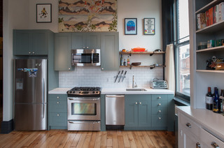 Spacious kitchen with light blue cabinets and stainless steel appliances