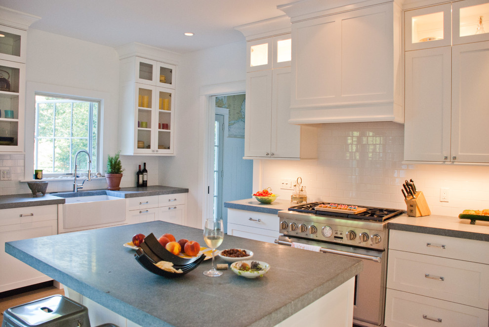 Inspiration for a farmhouse kitchen remodel in New York with subway tile backsplash, a farmhouse sink, shaker cabinets, white cabinets, white backsplash, stainless steel appliances and concrete countertops