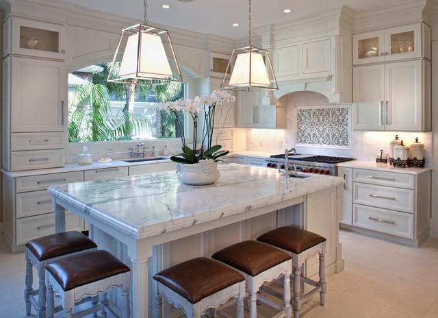 Foto di una cucina classica di medie dimensioni con lavello sottopiano, ante con riquadro incassato, ante bianche, paraspruzzi bianco, elettrodomestici in acciaio inossidabile, isola e pavimento con piastrelle in ceramica