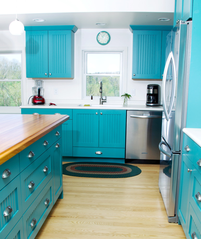 Inspiration for a mid-sized eclectic l-shaped light wood floor and brown floor eat-in kitchen remodel in Milwaukee with an integrated sink, blue cabinets, wood countertops, white backsplash, stainless steel appliances, an island, flat-panel cabinets and white countertops