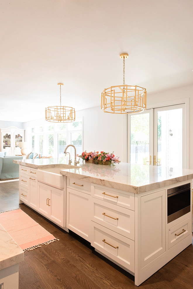 Inspiration for a large transitional medium tone wood floor and brown floor kitchen remodel in Austin with a farmhouse sink, recessed-panel cabinets, white cabinets, marble countertops, marble backsplash, white appliances and an island