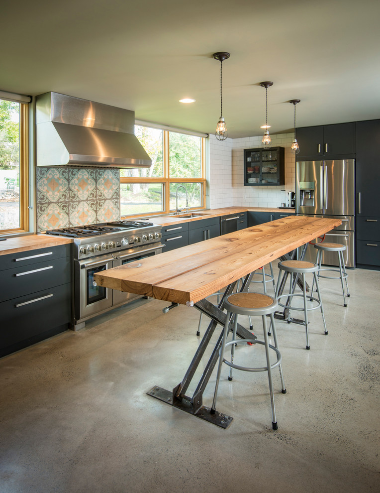 Eat-in kitchen - mid-sized industrial l-shaped concrete floor eat-in kitchen idea in Philadelphia with an undermount sink, flat-panel cabinets, black cabinets, wood countertops, white backsplash, subway tile backsplash, stainless steel appliances and an island