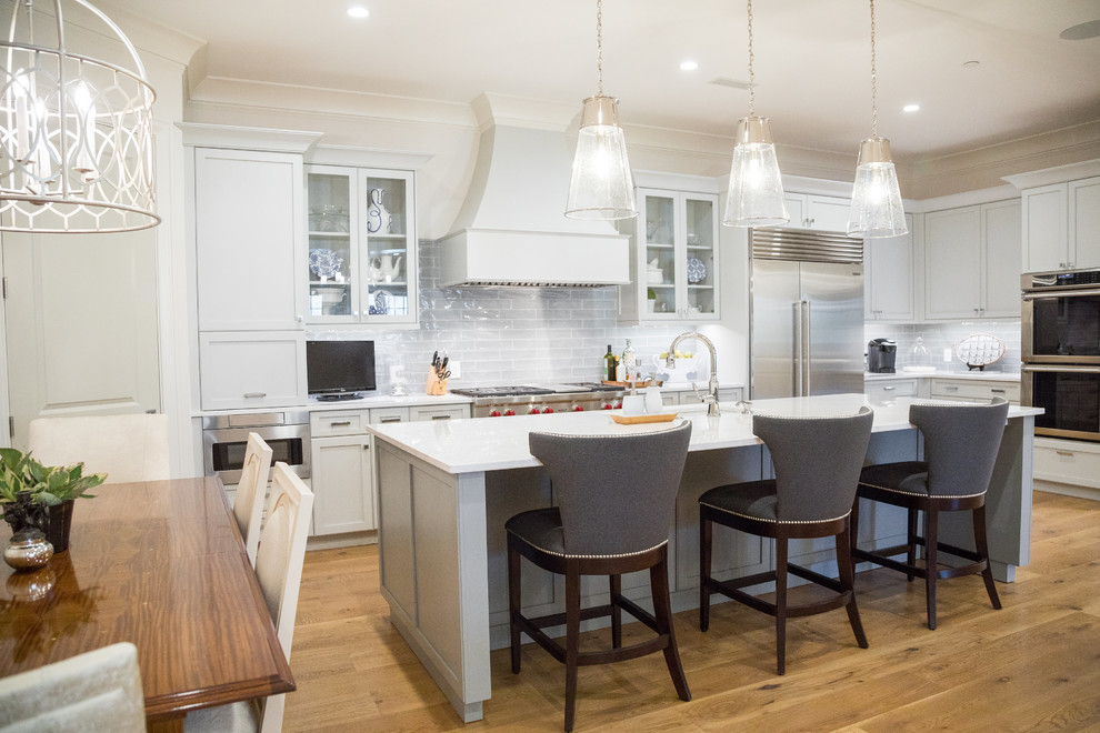 Elegant l-shaped medium tone wood floor eat-in kitchen photo in Other with glass-front cabinets, stainless steel appliances, an island, gray cabinets, gray backsplash, subway tile backsplash and white countertops