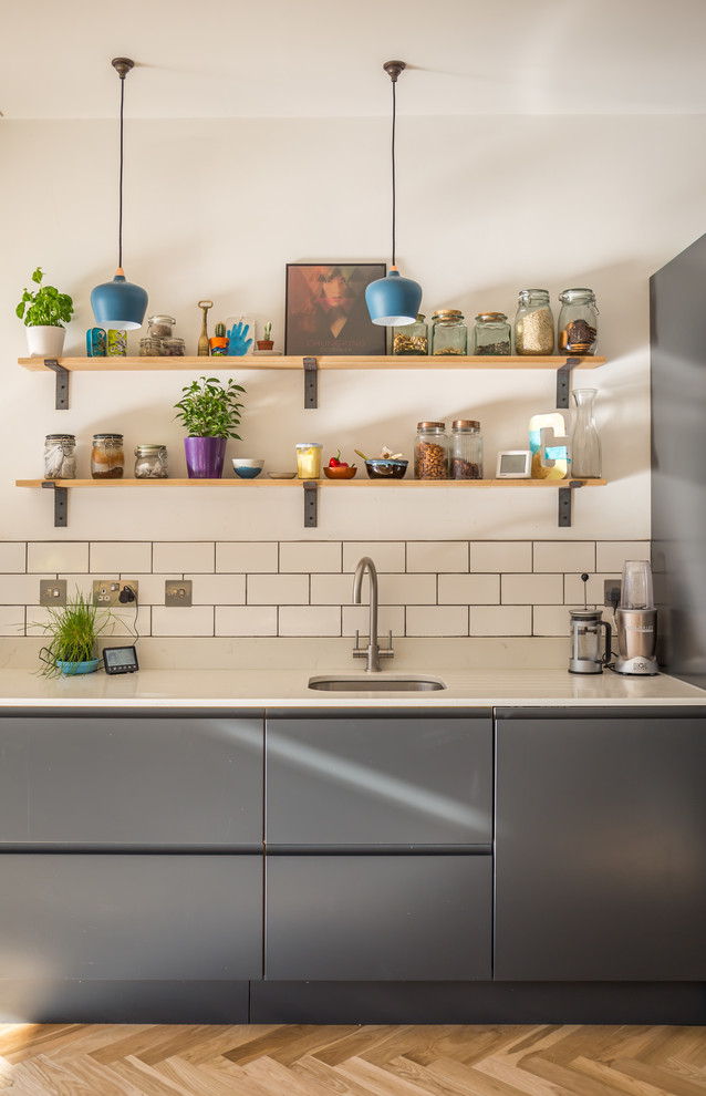 Inspiration for a contemporary light wood floor and brown floor kitchen remodel in Sussex with an undermount sink, flat-panel cabinets, gray cabinets, white backsplash and subway tile backsplash