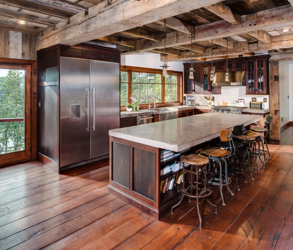 Immagine di una grande cucina stile rurale con lavello stile country, top in cemento, paraspruzzi bianco, paraspruzzi con piastrelle diamantate, elettrodomestici in acciaio inossidabile, top grigio, ante di vetro, ante in legno bruno e pavimento in legno massello medio