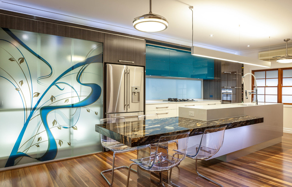 Design ideas for a mid-sized contemporary galley eat-in kitchen in Brisbane with stainless steel appliances, flat-panel cabinets, marble benchtops, medium hardwood floors and an island.