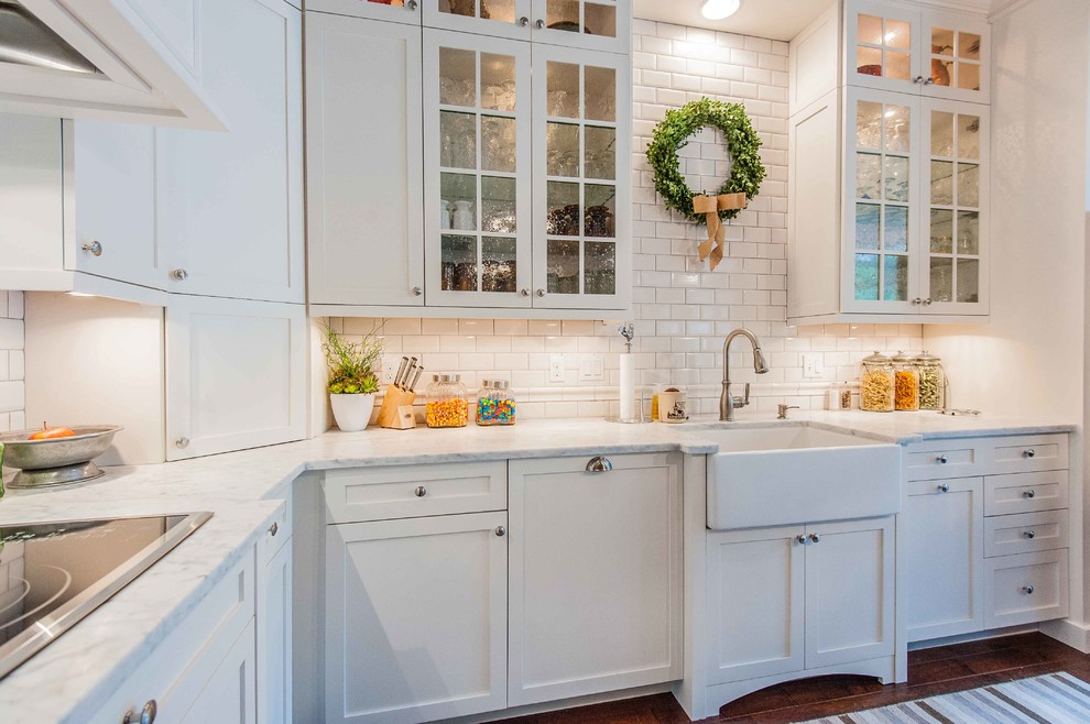 Example of an ornate kitchen design in Orlando with a farmhouse sink, white cabinets, white backsplash, subway tile backsplash and shaker cabinets