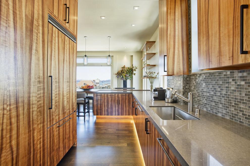 Kitchen - contemporary galley medium tone wood floor kitchen idea in San Francisco with an undermount sink, flat-panel cabinets, medium tone wood cabinets, multicolored backsplash, mosaic tile backsplash, paneled appliances and a peninsula