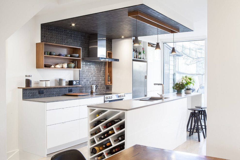Trendy galley open concept kitchen photo in Toronto with a double-bowl sink, flat-panel cabinets, white cabinets, black backsplash, mosaic tile backsplash, stainless steel appliances and an island