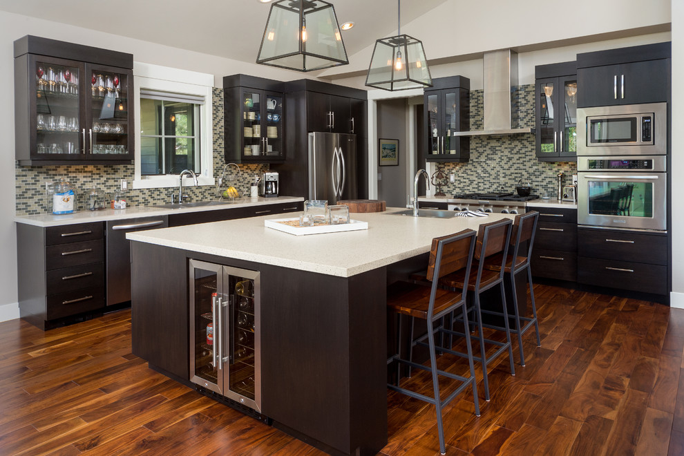 Example of a large trendy l-shaped kitchen design in Other with flat-panel cabinets, black cabinets, beige backsplash, mosaic tile backsplash and stainless steel appliances