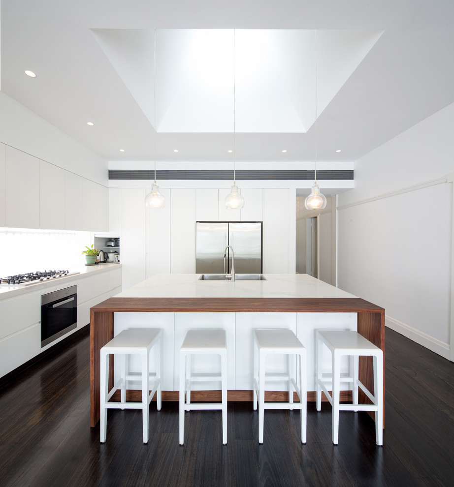 Design ideas for a contemporary l-shaped kitchen in Sydney with an undermount sink, flat-panel cabinets, white cabinets, white splashback, dark hardwood floors and an island.