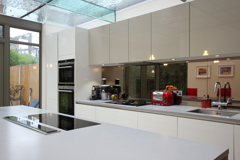 Trendy kitchen photo in London with mirror backsplash and an island