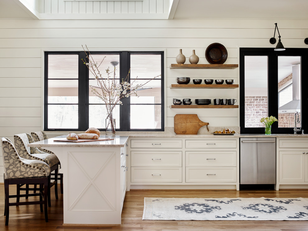 Example of a mid-sized country u-shaped medium tone wood floor and brown floor eat-in kitchen design in Atlanta with white cabinets, stainless steel appliances, a peninsula, an undermount sink, recessed-panel cabinets, marble countertops, white backsplash and white countertops