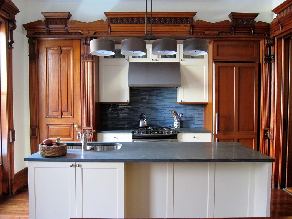 Example of a galley kitchen design in New York with glass tile backsplash, an undermount sink, recessed-panel cabinets, white cabinets and blue backsplash