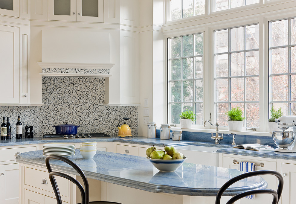 Eat-in kitchen - traditional l-shaped eat-in kitchen idea in New York with a farmhouse sink, white cabinets, beaded inset cabinets, marble countertops, multicolored backsplash and blue countertops