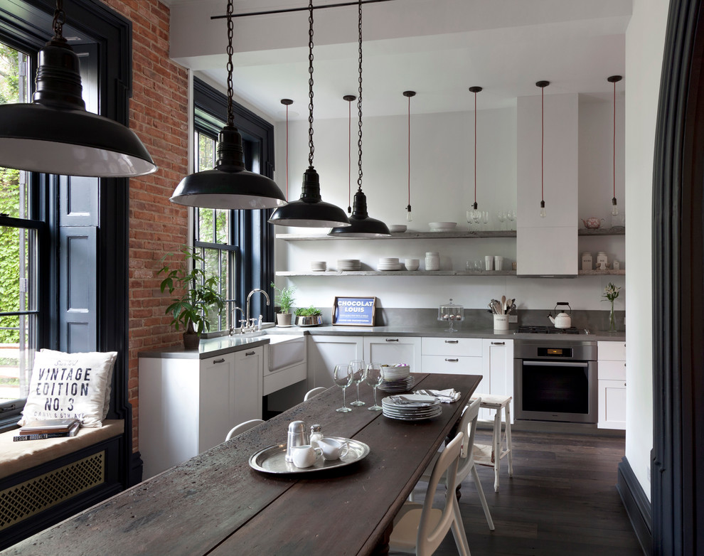 Urban dark wood floor eat-in kitchen photo in New York with a farmhouse sink, shaker cabinets, white cabinets, stainless steel appliances, no island and concrete countertops
