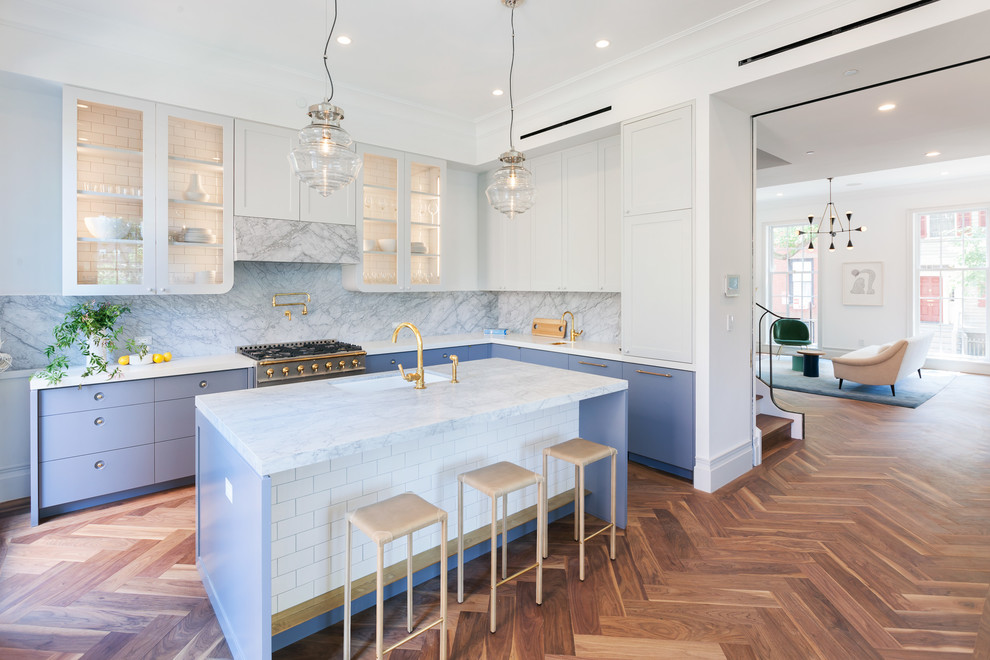 Kitchen - transitional l-shaped medium tone wood floor kitchen idea in New York with an undermount sink, glass-front cabinets, stone slab backsplash, stainless steel appliances and an island