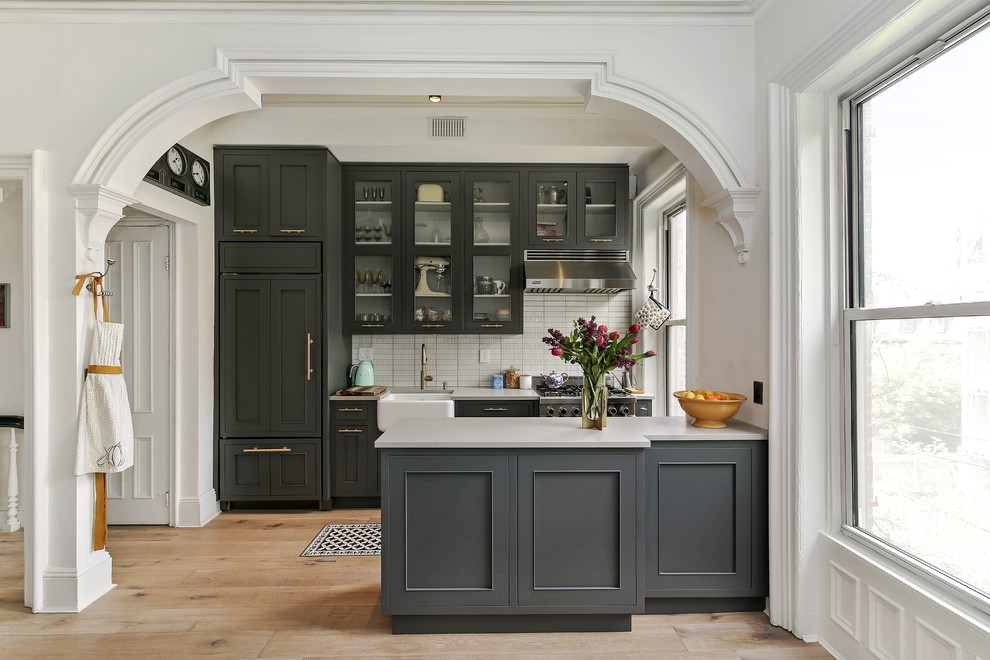 Inspiration for a mid-sized timeless galley medium tone wood floor and beige floor eat-in kitchen remodel in Philadelphia with a farmhouse sink, recessed-panel cabinets, gray cabinets, white backsplash, an island, solid surface countertops and ceramic backsplash