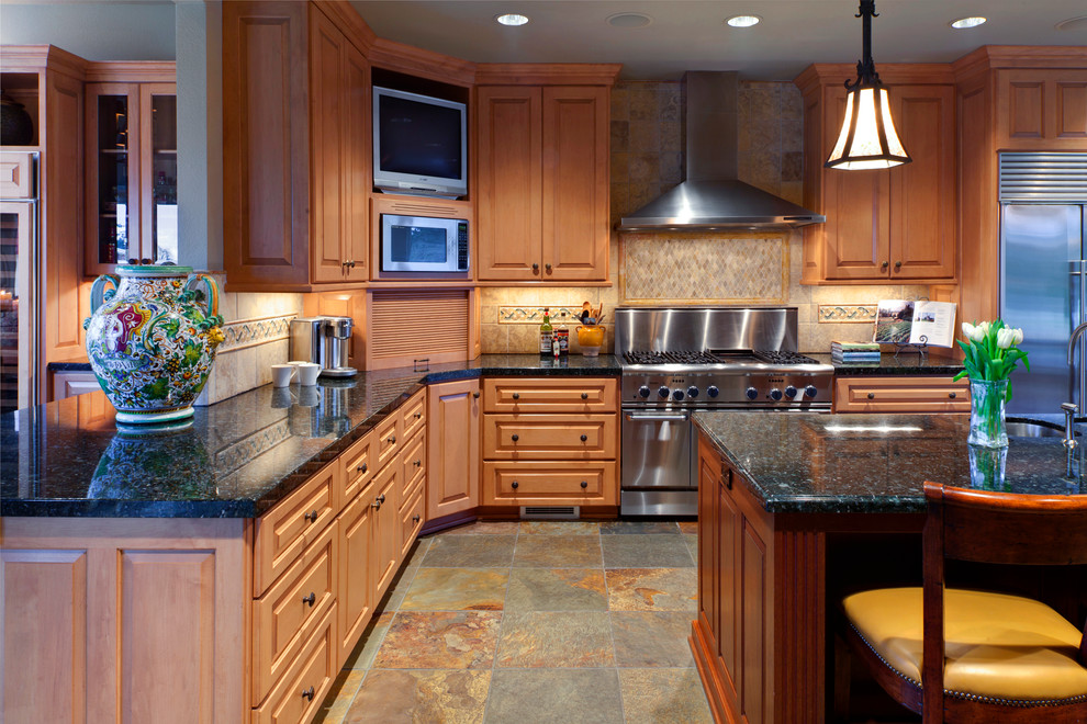 Example of a large classic l-shaped slate floor and multicolored floor kitchen design in Portland with an undermount sink, raised-panel cabinets, medium tone wood cabinets, granite countertops, brown backsplash, ceramic backsplash, stainless steel appliances and an island