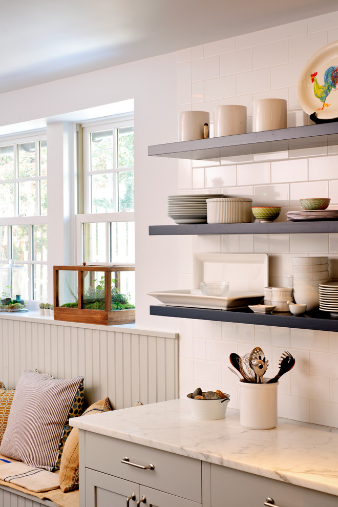 Inspiration for a mid-sized transitional l-shaped dark wood floor kitchen remodel in Philadelphia with gray cabinets, white backsplash, subway tile backsplash, marble countertops, a farmhouse sink, open cabinets, stainless steel appliances and an island