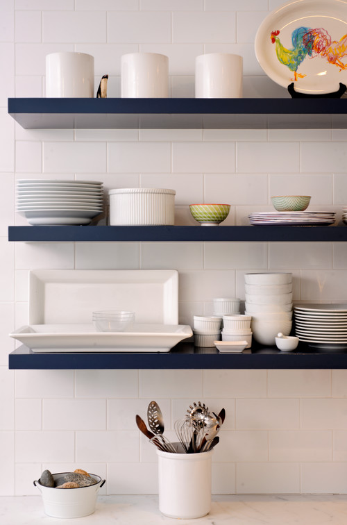 Dark Navy Blue floating shelves in a bright white kitchen with a contrasting White subway-tile wall to display dishware.