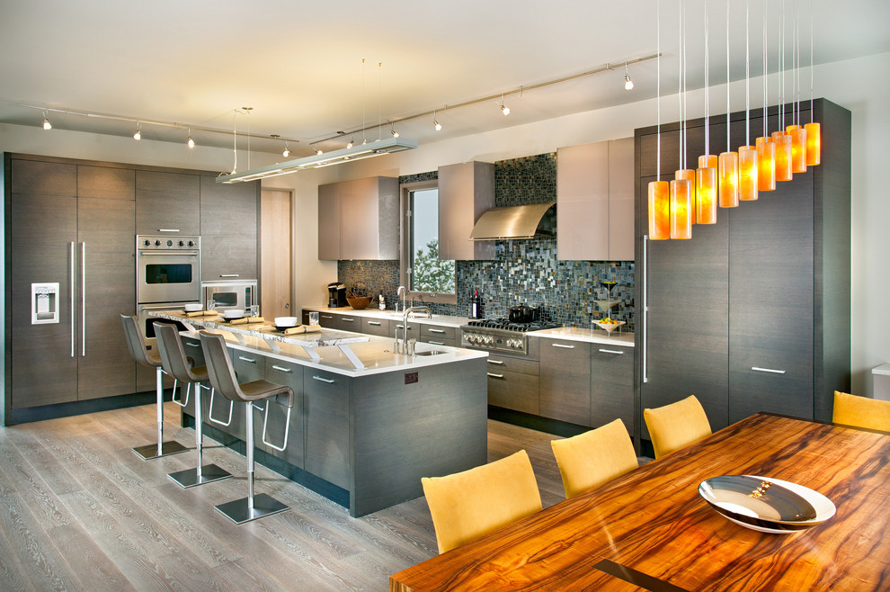 Eat-in kitchen - huge contemporary galley light wood floor and gray floor eat-in kitchen idea in Atlanta with paneled appliances, flat-panel cabinets, gray cabinets, quartz countertops, an island, an undermount sink, metallic backsplash and glass tile backsplash