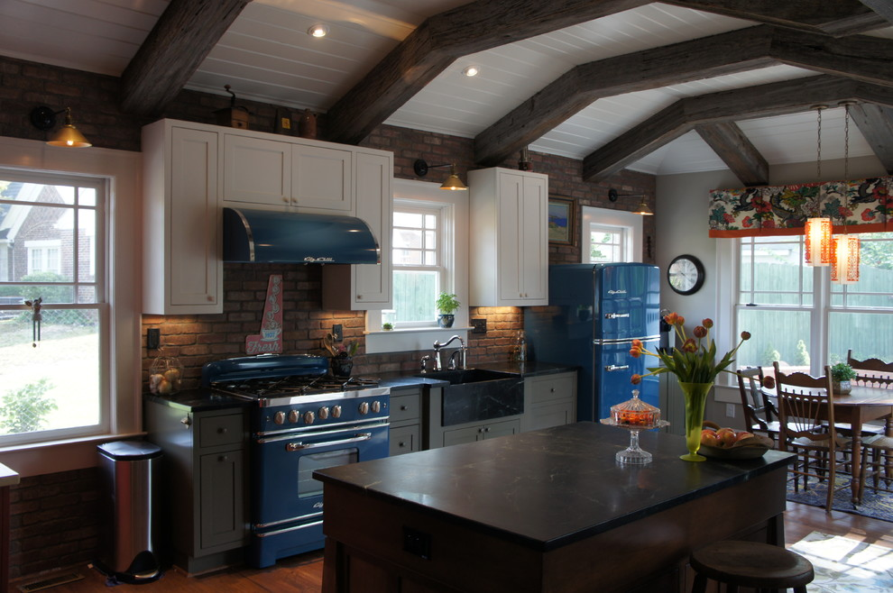 Example of a mid-sized country u-shaped light wood floor and brown floor eat-in kitchen design in Atlanta with a farmhouse sink, shaker cabinets, white cabinets, colored appliances, an island, soapstone countertops and brick backsplash