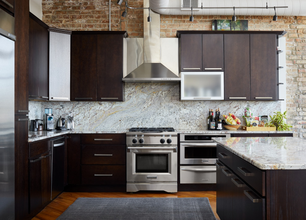 Inspiration for a large industrial l-shaped medium tone wood floor eat-in kitchen remodel in Chicago with a drop-in sink, flat-panel cabinets, dark wood cabinets, marble countertops, multicolored backsplash, marble backsplash, stainless steel appliances and an island