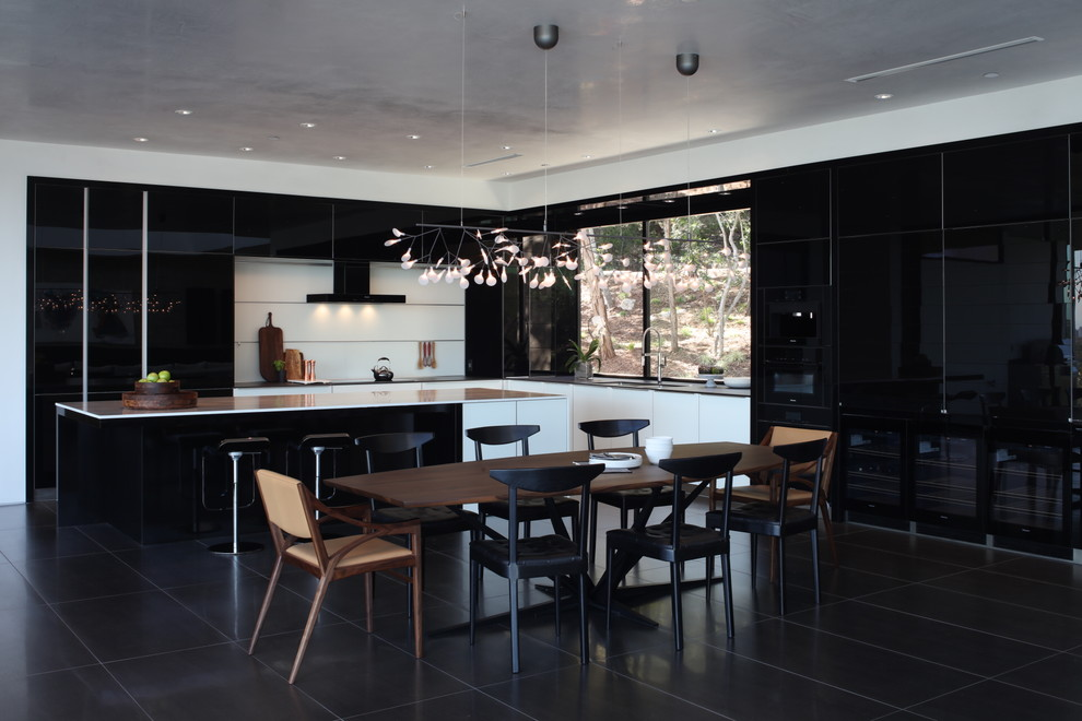 Inspiration for a contemporary l-shaped black floor and porcelain floor eat-in kitchen remodel in Austin with flat-panel cabinets, black cabinets, white backsplash, an island, an undermount sink, marble countertops, glass sheet backsplash and black appliances