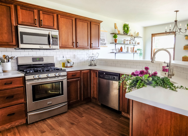 Mid-sized farmhouse u-shaped laminate floor and brown floor eat-in kitchen photo in Other with a farmhouse sink, raised-panel cabinets, medium tone wood cabinets, solid surface countertops, white backsplash, subway tile backsplash, stainless steel appliances, a peninsula and white countertops