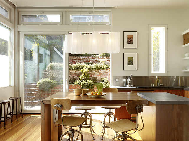 Minimalist light wood floor eat-in kitchen photo in San Francisco with flat-panel cabinets, light wood cabinets, soapstone countertops, metallic backsplash and stainless steel appliances
