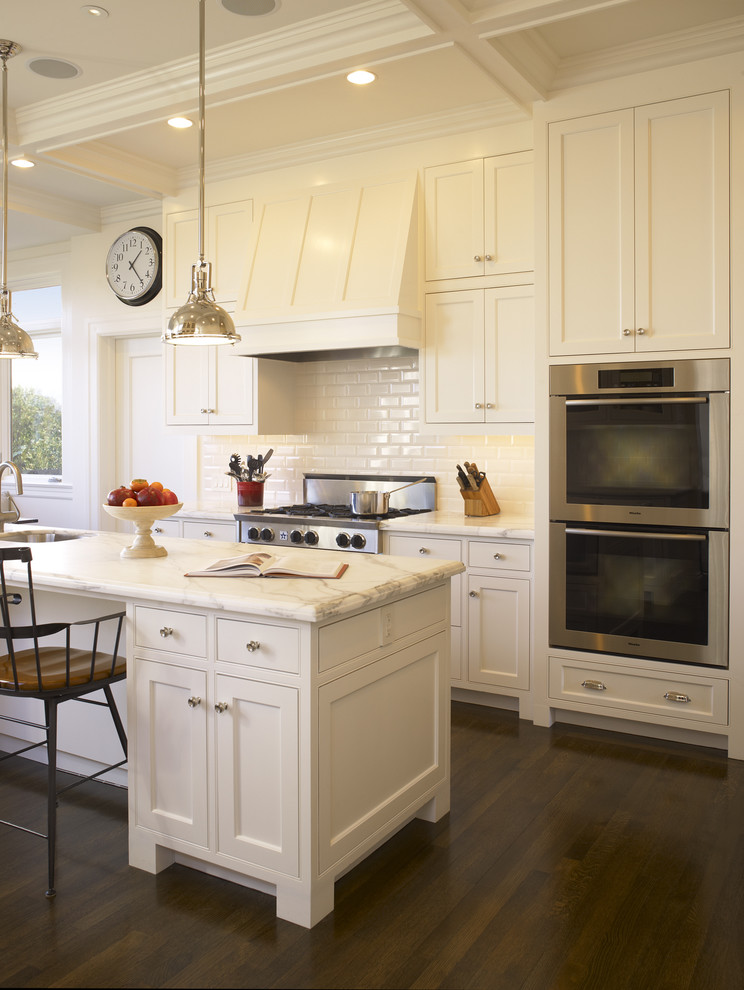 Elegant kitchen photo in San Francisco with beaded inset cabinets, white cabinets, marble countertops, white backsplash, subway tile backsplash and stainless steel appliances