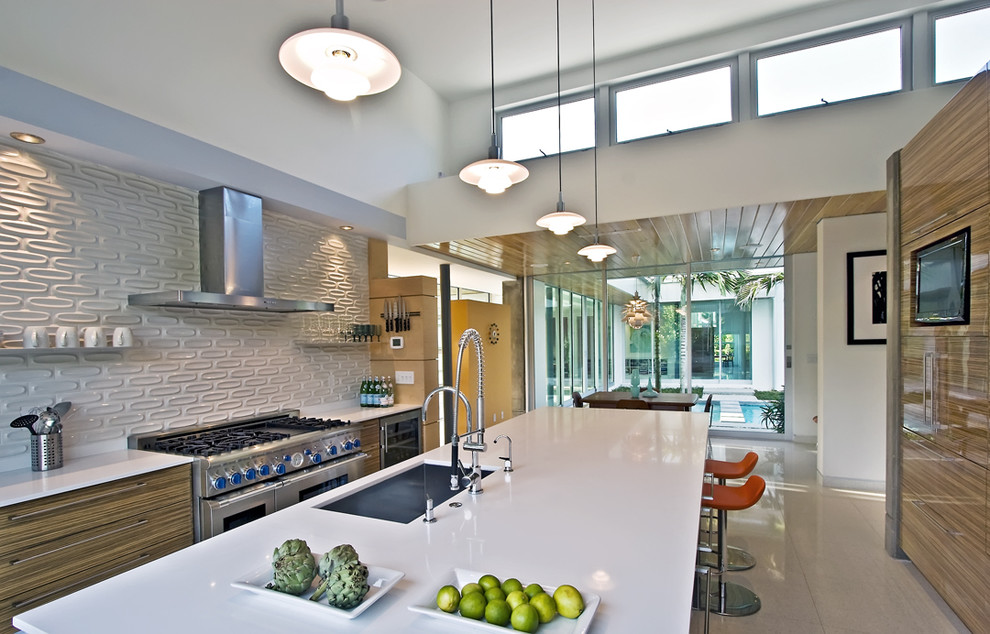 Example of a minimalist galley eat-in kitchen design in Miami with an undermount sink, flat-panel cabinets, light wood cabinets, quartz countertops, white backsplash, subway tile backsplash and stainless steel appliances