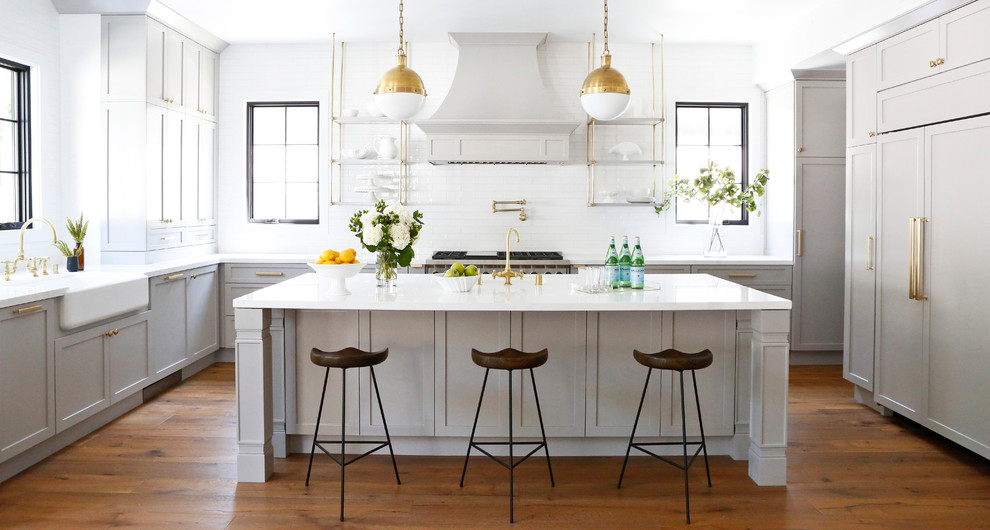 Mid-sized transitional medium tone wood floor eat-in kitchen photo in Los Angeles with white backsplash, subway tile backsplash, stainless steel appliances and an island