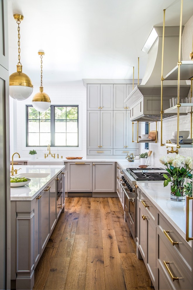 Example of a mid-sized transitional medium tone wood floor enclosed kitchen design in Los Angeles with white backsplash, subway tile backsplash, stainless steel appliances, an island, shaker cabinets and beige cabinets