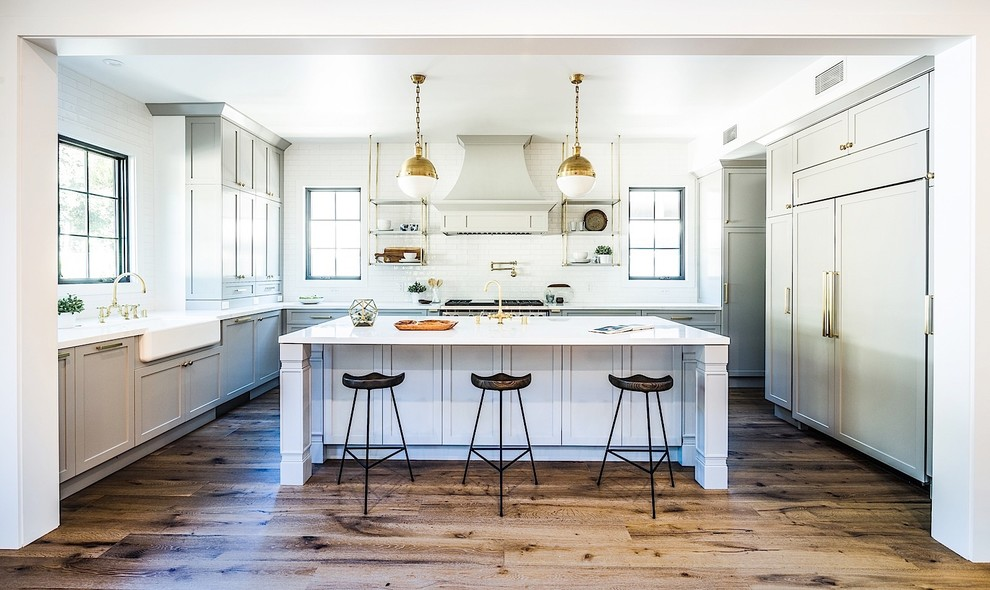 Inspiration for a mid-sized transitional medium tone wood floor eat-in kitchen remodel in Los Angeles with white backsplash, subway tile backsplash, stainless steel appliances and an island