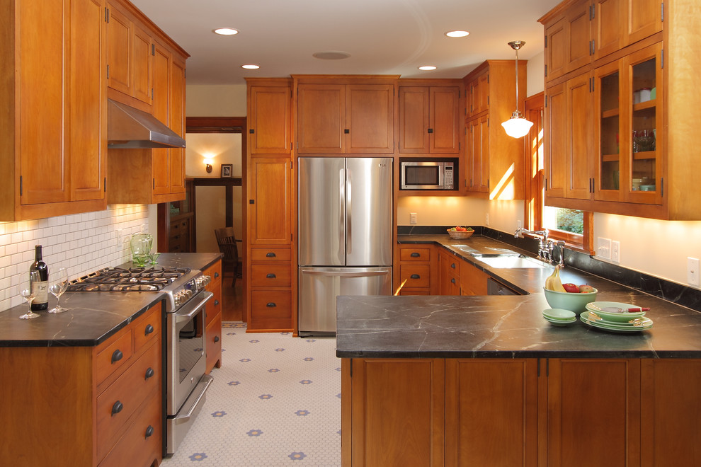 Kitchen - craftsman u-shaped kitchen idea in Minneapolis with recessed-panel cabinets, soapstone countertops, medium tone wood cabinets, white backsplash, subway tile backsplash and stainless steel appliances