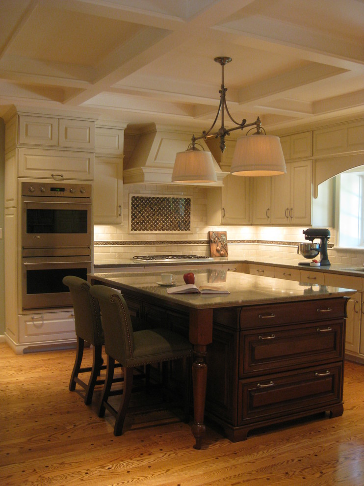 Example of a large classic u-shaped medium tone wood floor and brown floor open concept kitchen design in Houston with an undermount sink, raised-panel cabinets, dark wood cabinets, granite countertops, stainless steel appliances, an island, beige backsplash and limestone backsplash