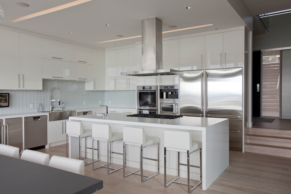Inspiration for a contemporary l-shaped eat-in kitchen remodel in Vancouver with a farmhouse sink, stainless steel appliances, flat-panel cabinets, white cabinets, white backsplash, glass tile backsplash and quartz countertops