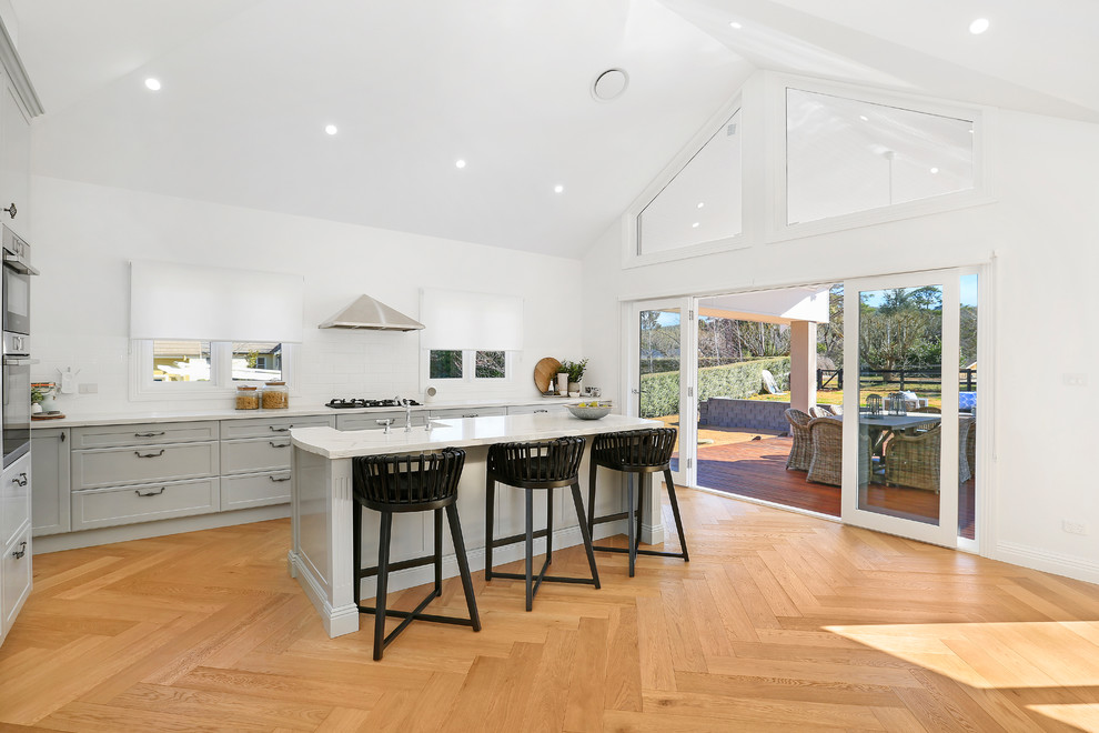 Design ideas for an expansive country l-shaped open plan kitchen in Wollongong with a farmhouse sink, shaker cabinets, grey cabinets, quartz benchtops, white splashback, ceramic splashback, stainless steel appliances, an island, medium hardwood floors, brown floor and white benchtop.