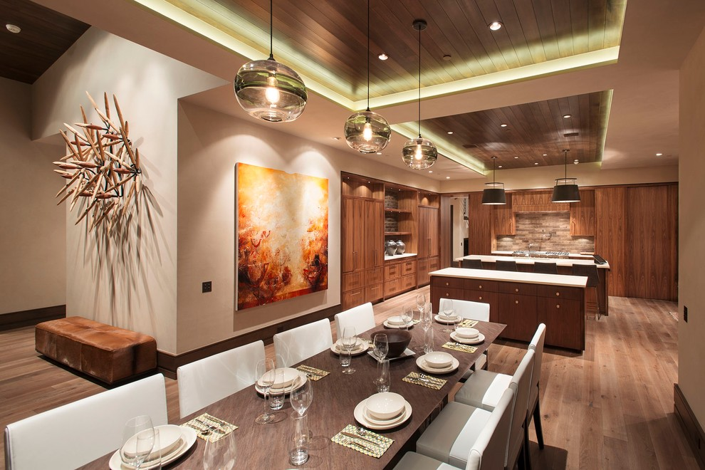 Trendy u-shaped eat-in kitchen photo in Denver with medium tone wood cabinets, brown backsplash and paneled appliances