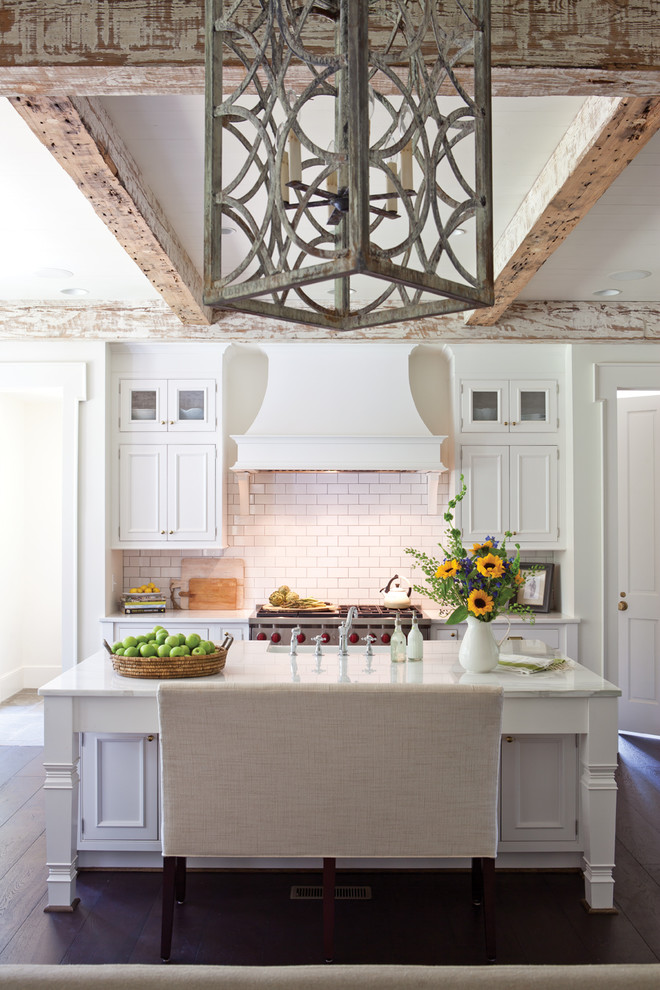 Eat-in kitchen - mid-sized cottage single-wall dark wood floor and brown floor eat-in kitchen idea in DC Metro with a farmhouse sink, beaded inset cabinets, white cabinets, marble countertops, white backsplash, subway tile backsplash, an island and white countertops