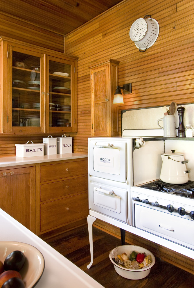 Inspiration for a shabby-chic style kitchen remodel in Minneapolis with glass-front cabinets, medium tone wood cabinets and white appliances