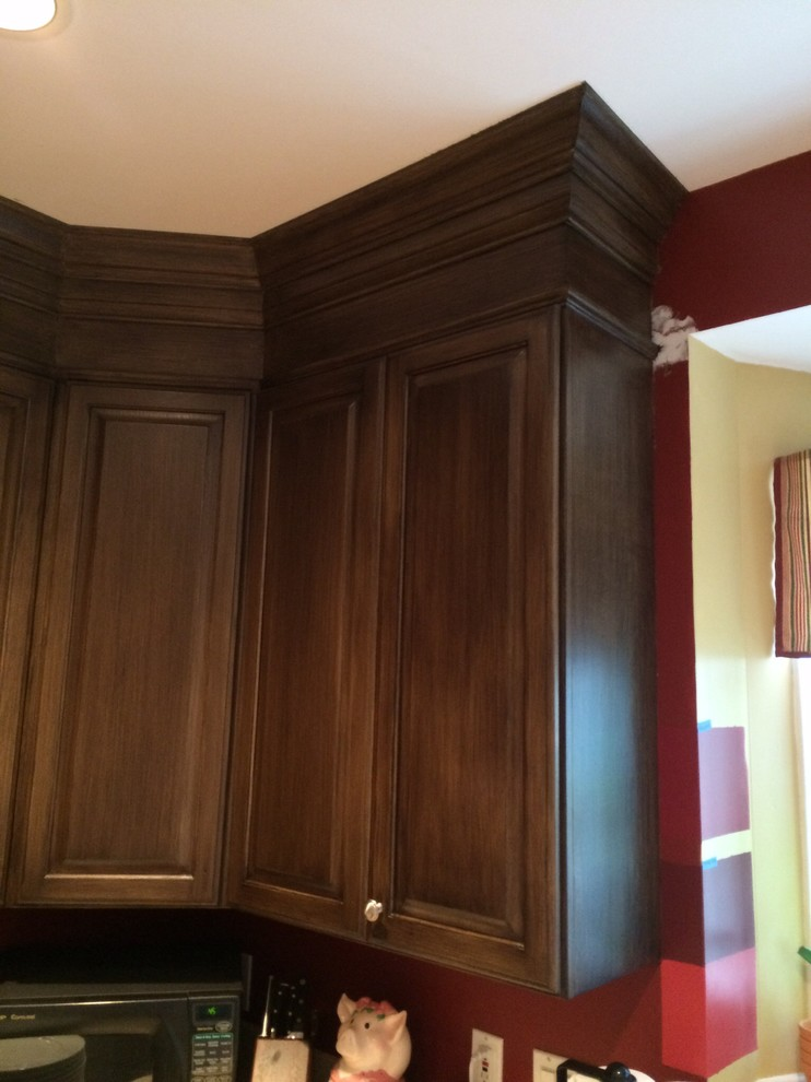 Example of an arts and crafts kitchen design in Cincinnati with raised-panel cabinets and dark wood cabinets