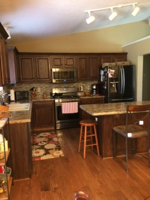 Inspiration for a mid-sized timeless l-shaped dark wood floor and brown floor enclosed kitchen remodel in Cincinnati with a double-bowl sink, raised-panel cabinets, dark wood cabinets, granite countertops, multicolored backsplash, matchstick tile backsplash, stainless steel appliances and an island