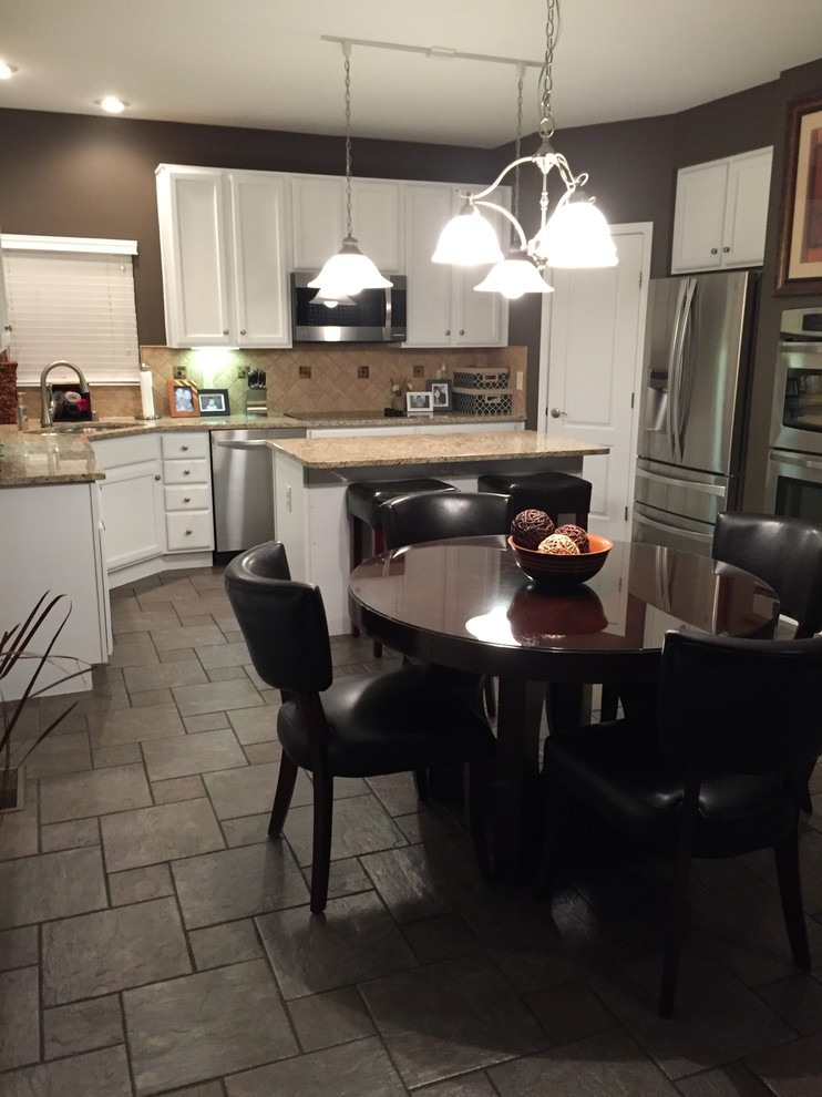Eat-in kitchen - mid-sized traditional l-shaped gray floor eat-in kitchen idea in Cincinnati with a double-bowl sink, recessed-panel cabinets, white cabinets, granite countertops, beige backsplash, stone tile backsplash, stainless steel appliances and an island