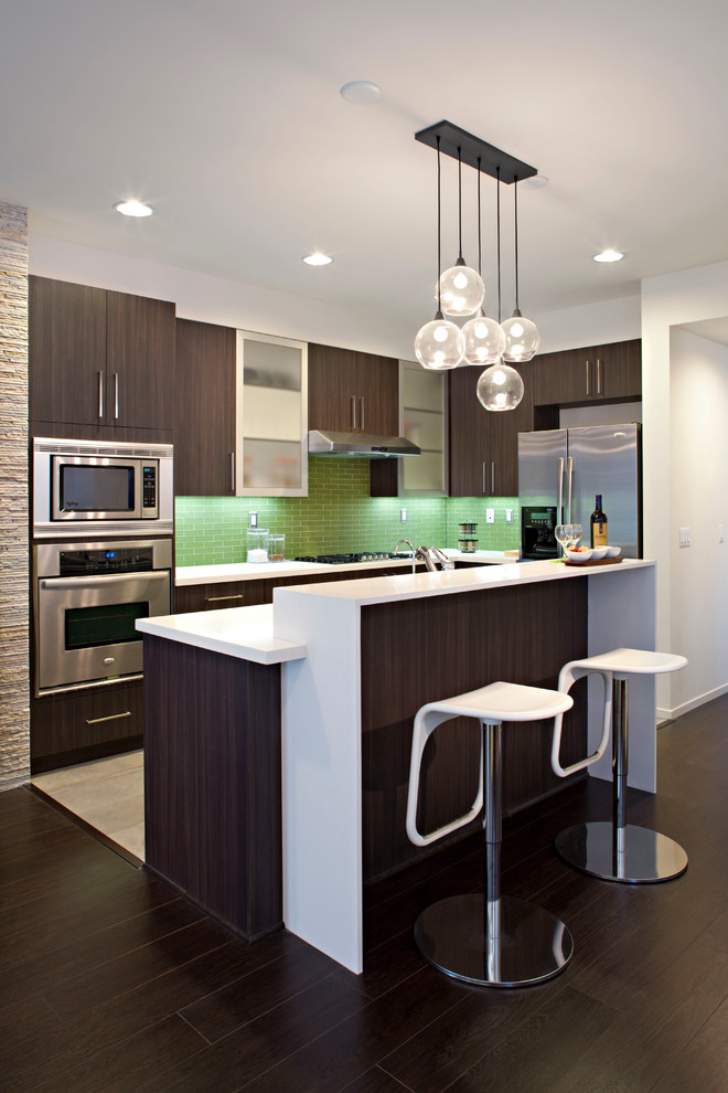 Example of a mid-sized trendy l-shaped dark wood floor open concept kitchen design in Los Angeles with stainless steel appliances, an undermount sink, flat-panel cabinets, dark wood cabinets, quartz countertops, green backsplash, subway tile backsplash and an island