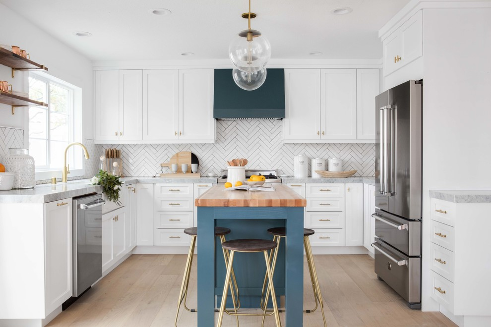 Example of a mid-sized transitional u-shaped light wood floor and beige floor open concept kitchen design in Orange County with a farmhouse sink, white cabinets, marble countertops, white backsplash, ceramic backsplash, an island, shaker cabinets and stainless steel appliances